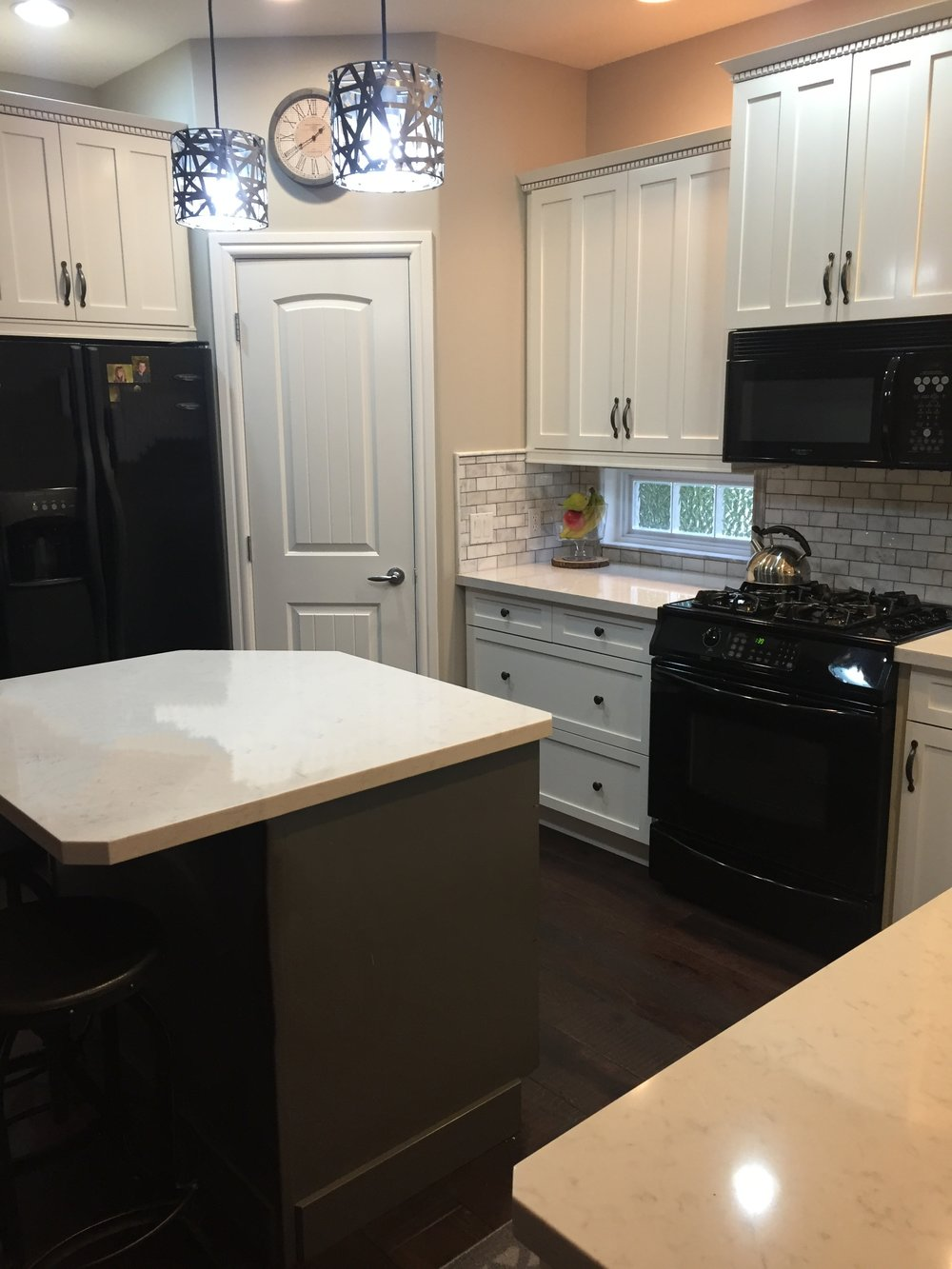 Painted cabinets, light main cabinets with darker island, marble backsplash, quartz countertops