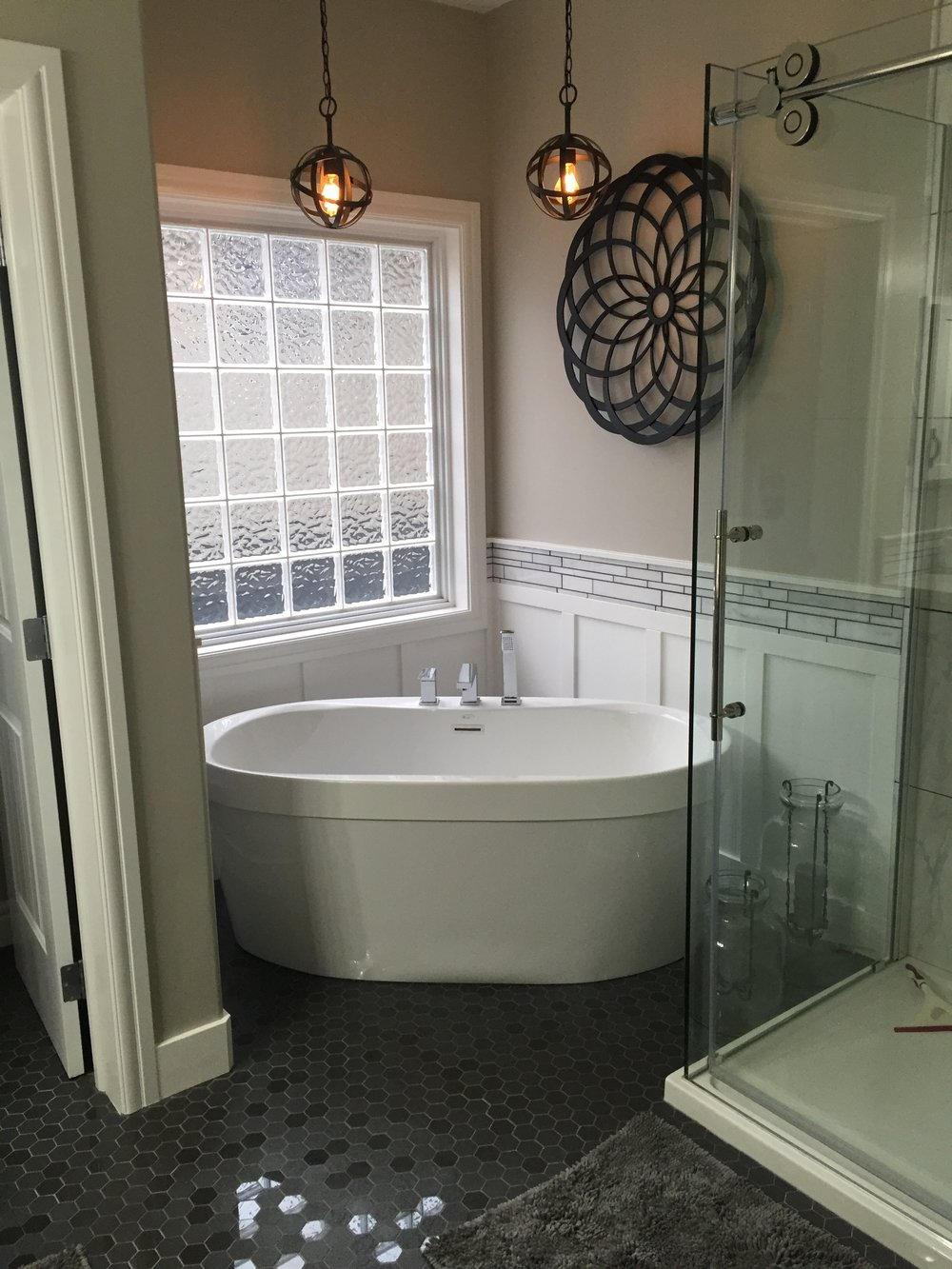 Updated corner freestanding soaker tub, hexagon floor tile, marble mosaics, rolling glass door hardware