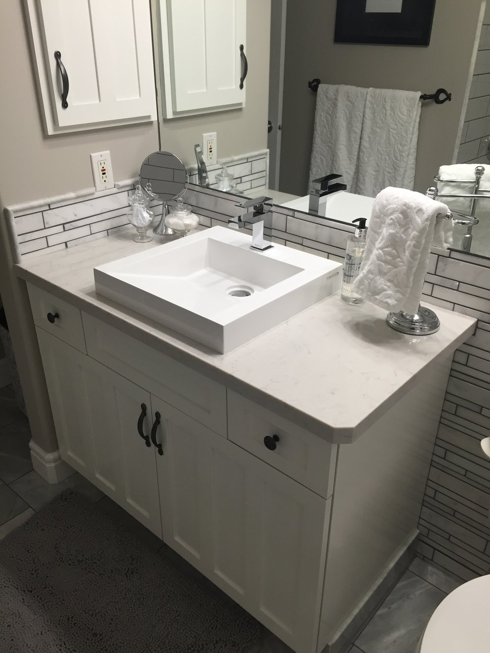 painted white cabinets, white quartz countertop, marble mosaics.