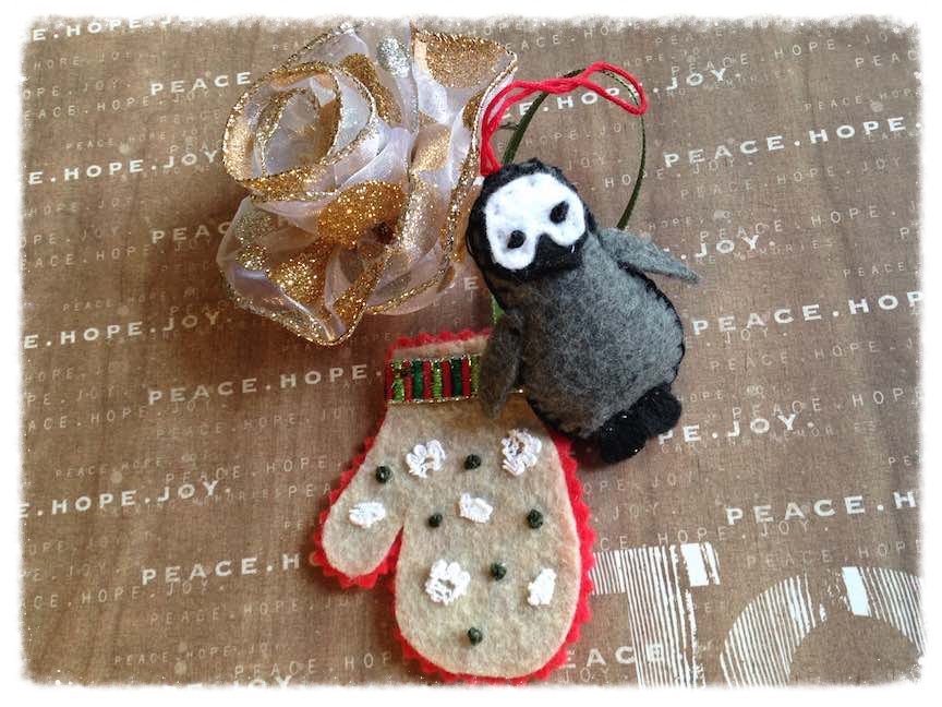 Fabric DIY Christmas ornaments: felt mitten, stuffed penguin, and ribbon rose.