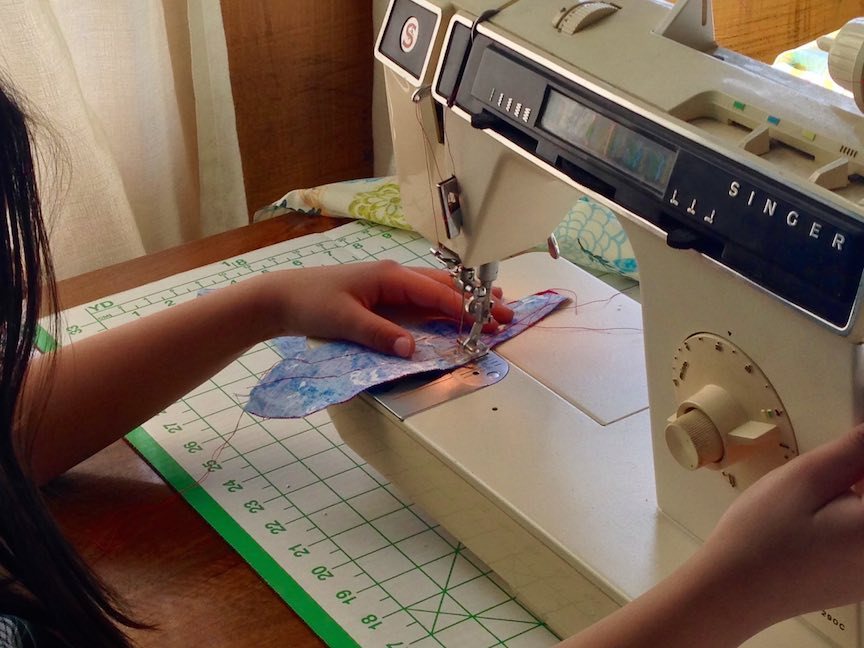 A young sewing student hard at work on her first machine project, a letter pillow.