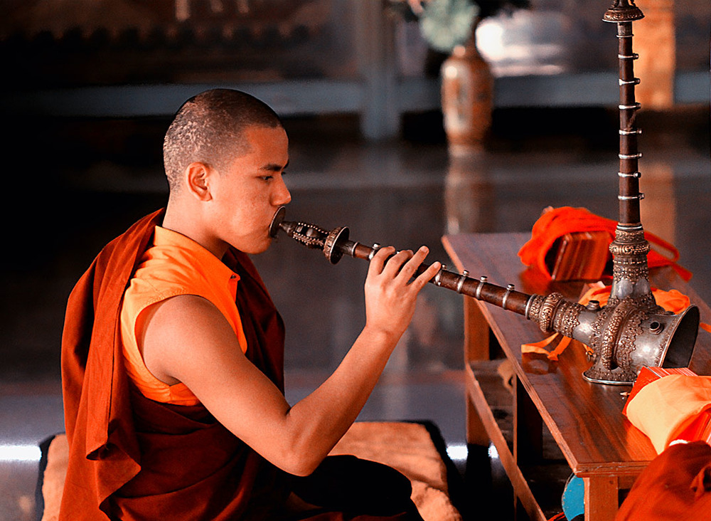 A Buddhist monk blowing his trumpet during a ritual