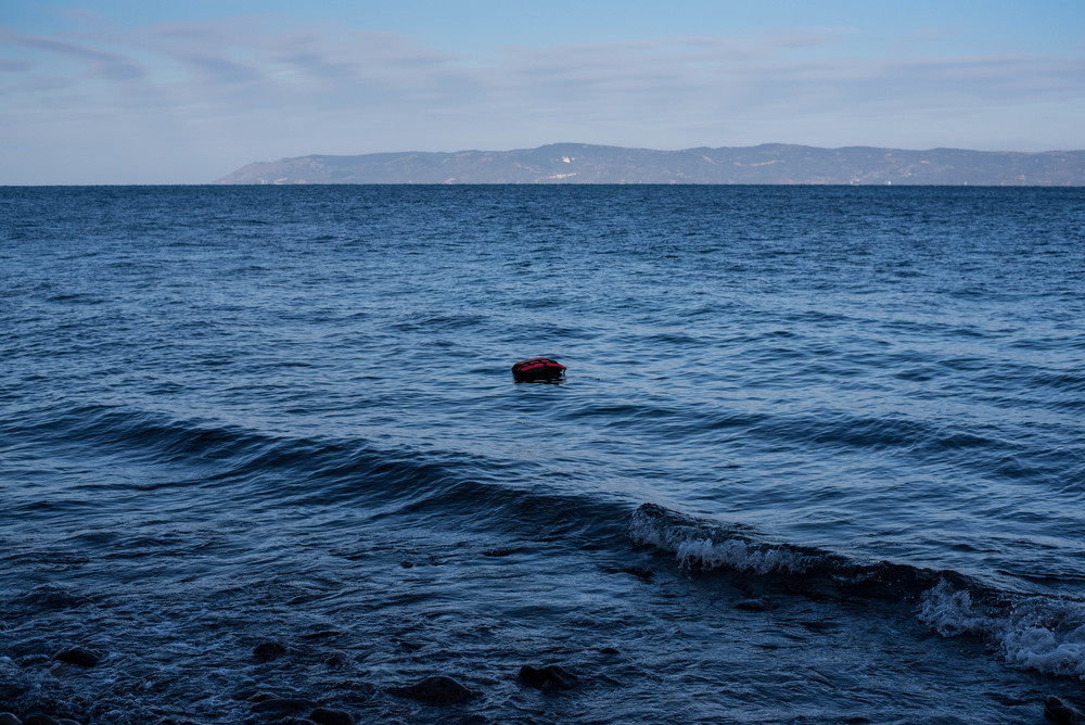 A lone life jacket drifts on the water near the shores of Lesvos, Greece. Most of the life jackets sold to refugees in Turkey are not actually life-saving; instead they're made from cheap pieces of foam and misleadingly display Japanese brand names like Yamaha.