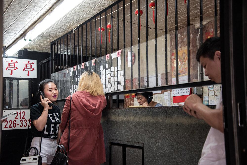 Two women stand inside a restaurant employment center on Eldridge Street in Manhattan's Chinatown.