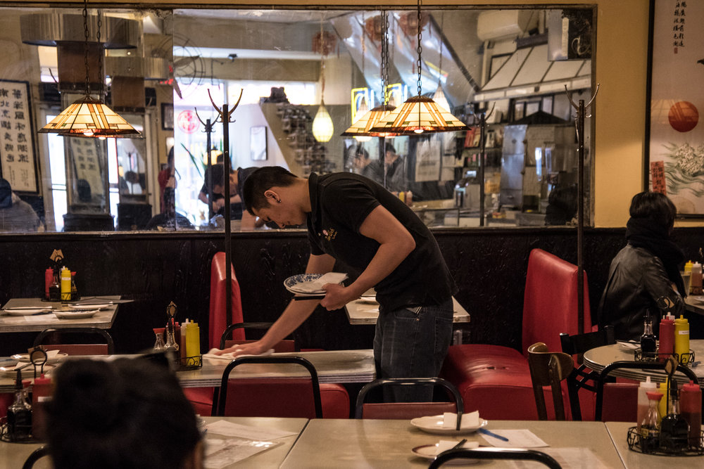A worker cleans a table at Nom Wah in Chinatown.