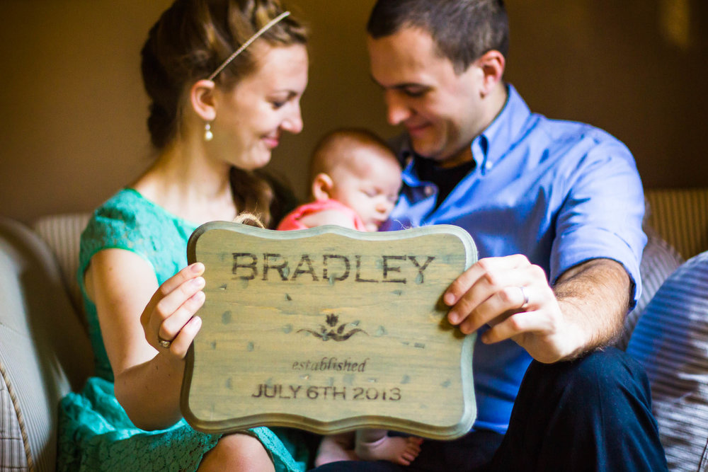 Seattle Newborn Photographer | G. Lin Photography | Family holding sign with baby sleeping