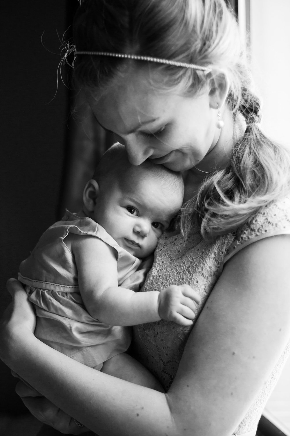 Seattle Lifestyle Family Photography | By G. Lin Photography | Mother holding baby in arms by window