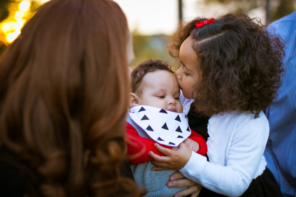 Durham Family Photographer | G. Lin Photography | Girl holding baby brother and kissing him on head