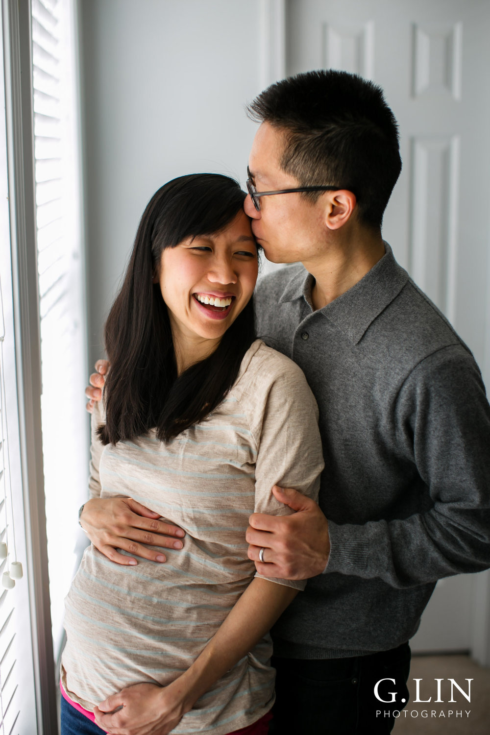 Durham Maternity Photography | G. Lin Photography | Couple standing by window and laughing