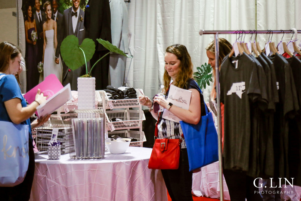 Raleigh Event Photographer | G. Lin Photography | Guests at booth looking at wedding merchandise