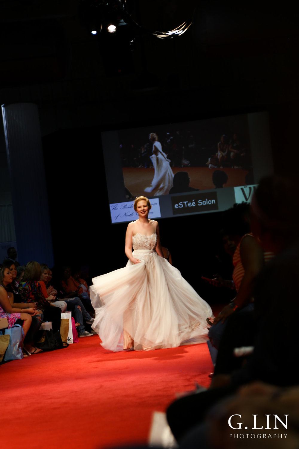 Raleigh Event Photographer | G. Lin Photography | Female model waving wedding dress during fashion show