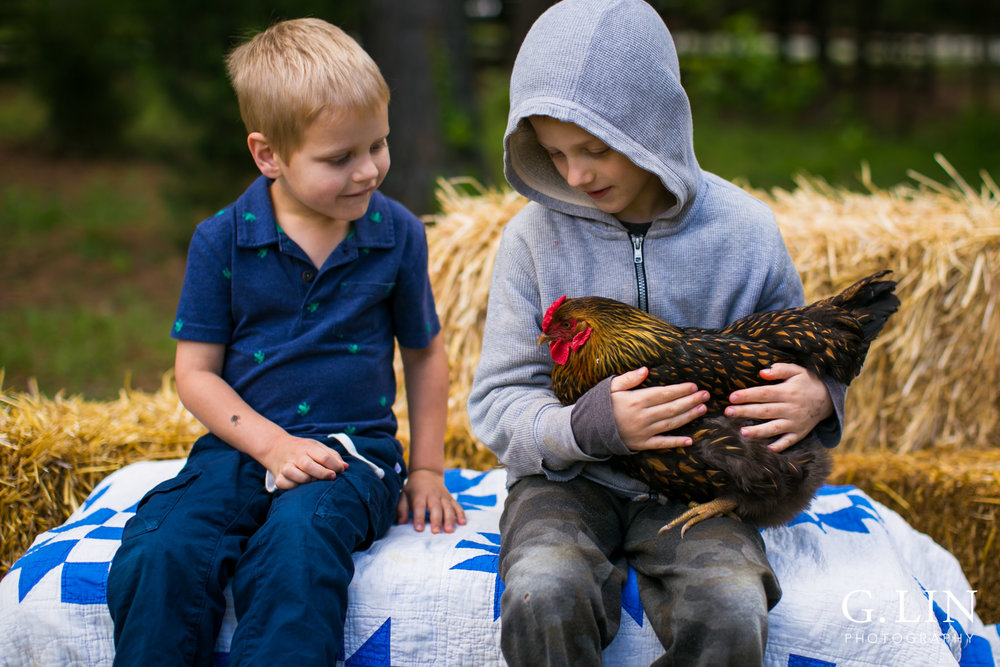 G. Lin Photography | Raleigh Event Photographer | Two boys on hay stack holding chicken