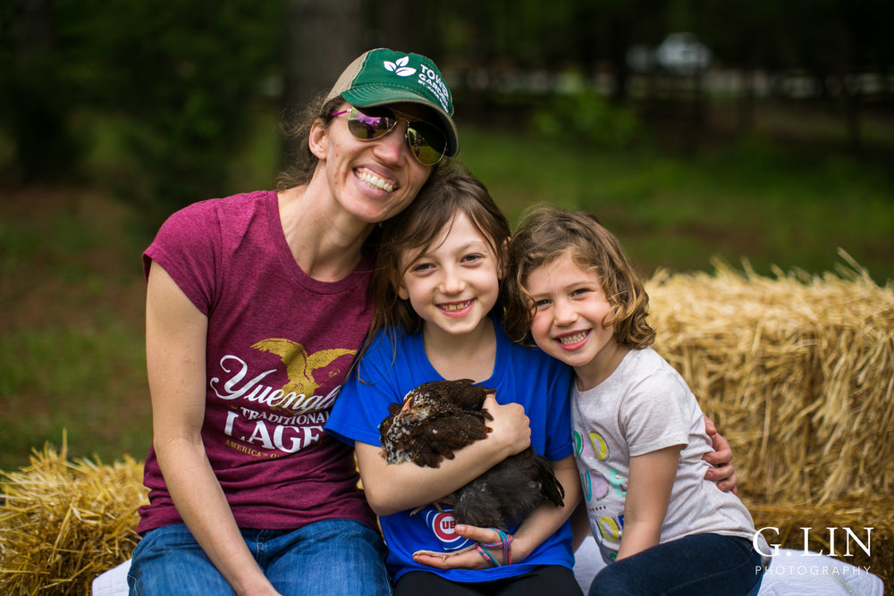 G. Lin Photography | Raleigh Event Photographer | Mom and two girls sitting on hay stack and smiling