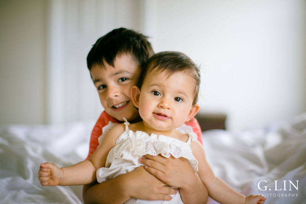 G. Lin Photography | Durham Family Photographer | Boy holding baby sister on white bed