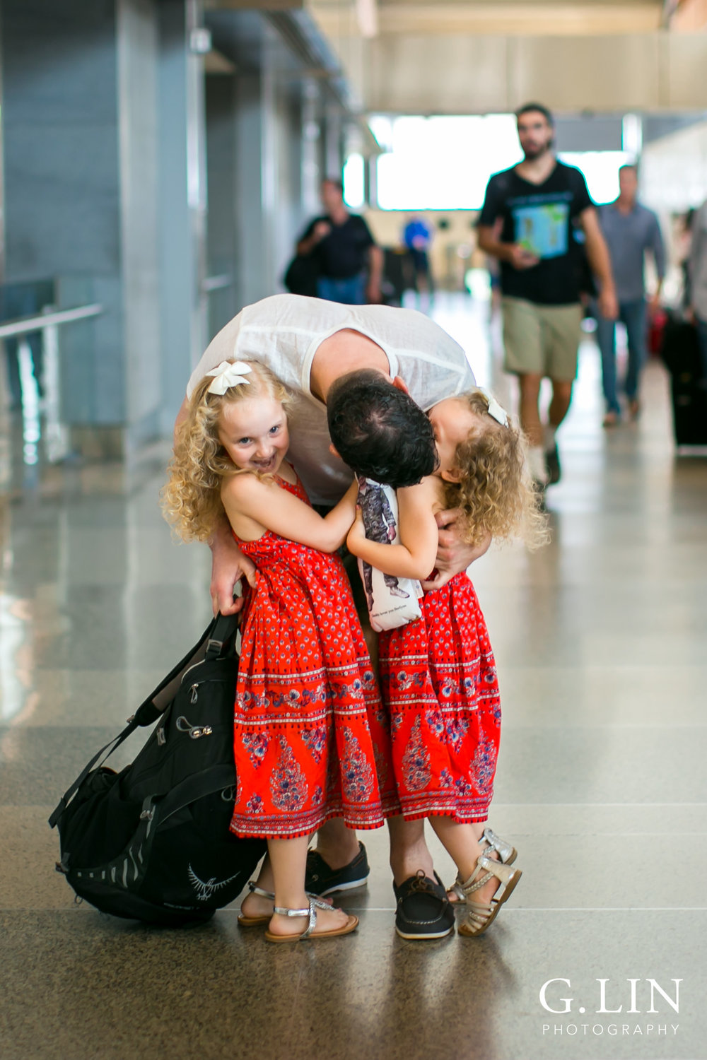 Raleigh Family Photographer | G. Lin Photography | two girls hugging their dad and welcoming him home
