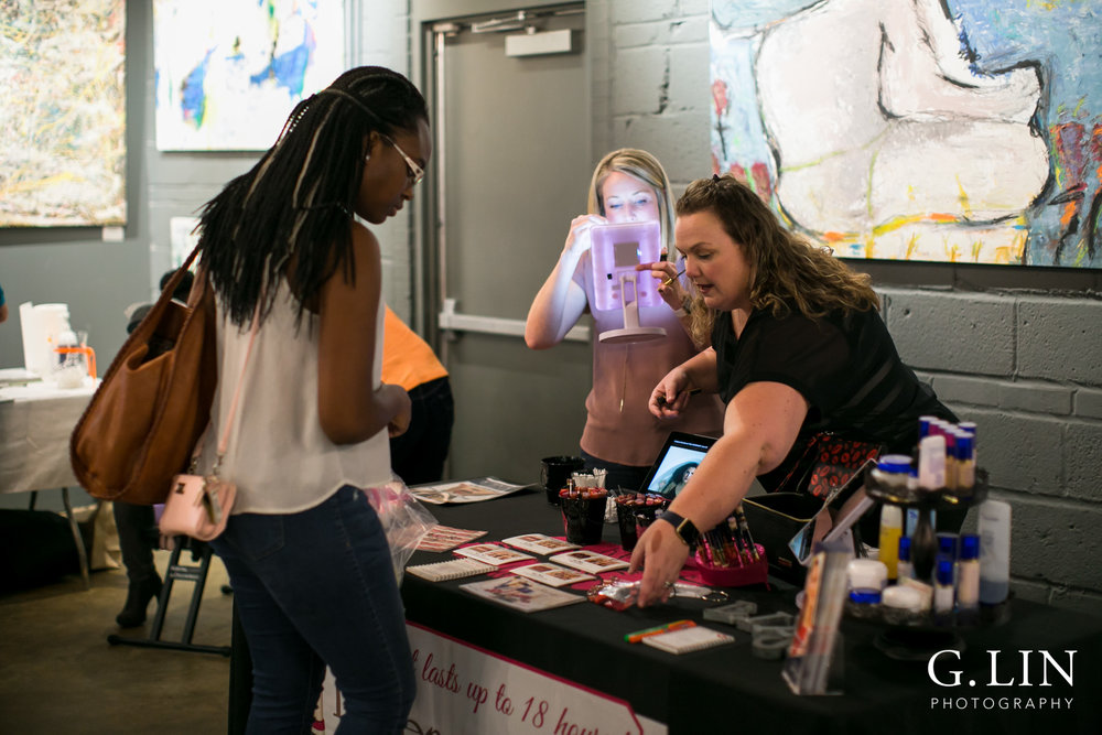 Raleigh Event Photographer | G. Lin Photography | Woman showing lip products to customer