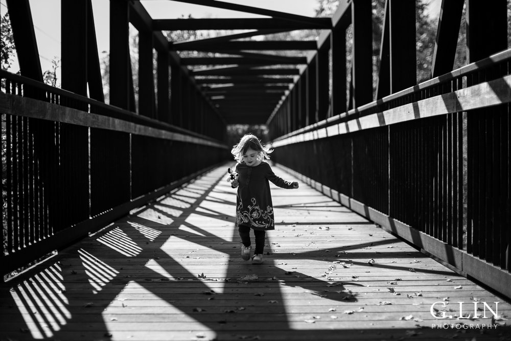 Durham Family Photographer | G. Lin Photography | Little girl running across a bridge towards camera