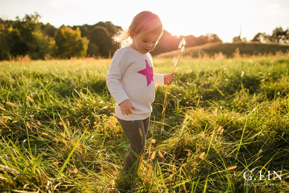 Raleigh Family Photographer | G. Lin Photography | Little girl playing in the open field with warm sunlight