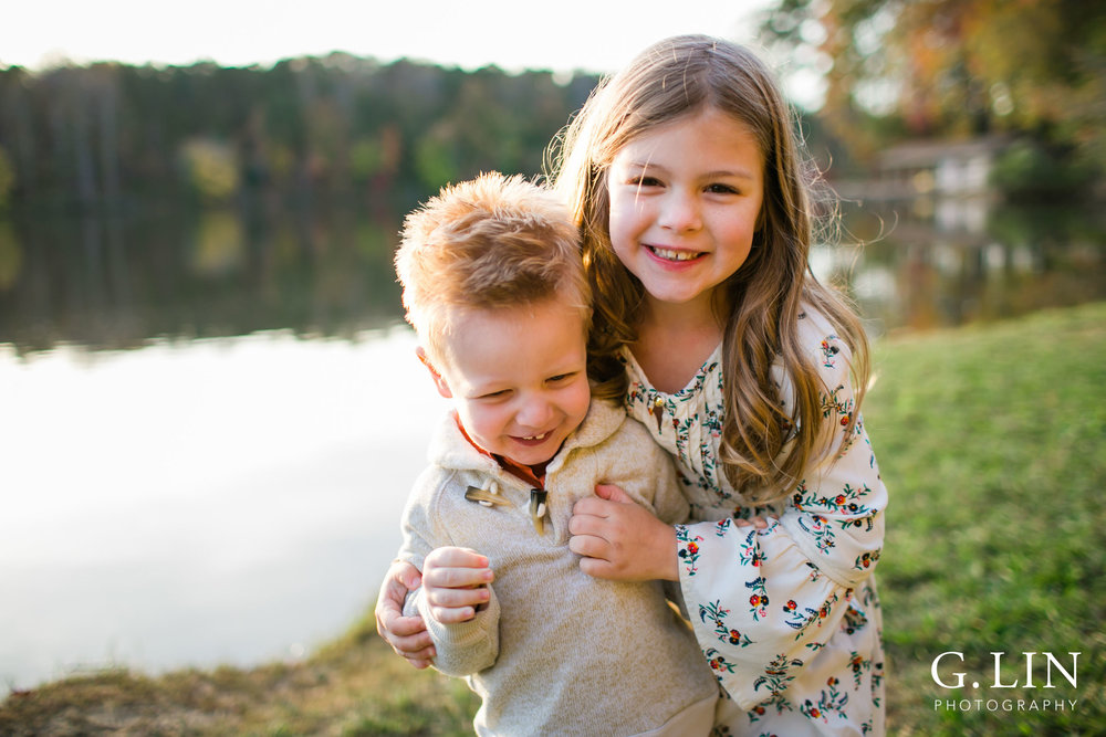 Raleigh Family Photographer | G. Lin Photography | sister hugging little brother by the lake