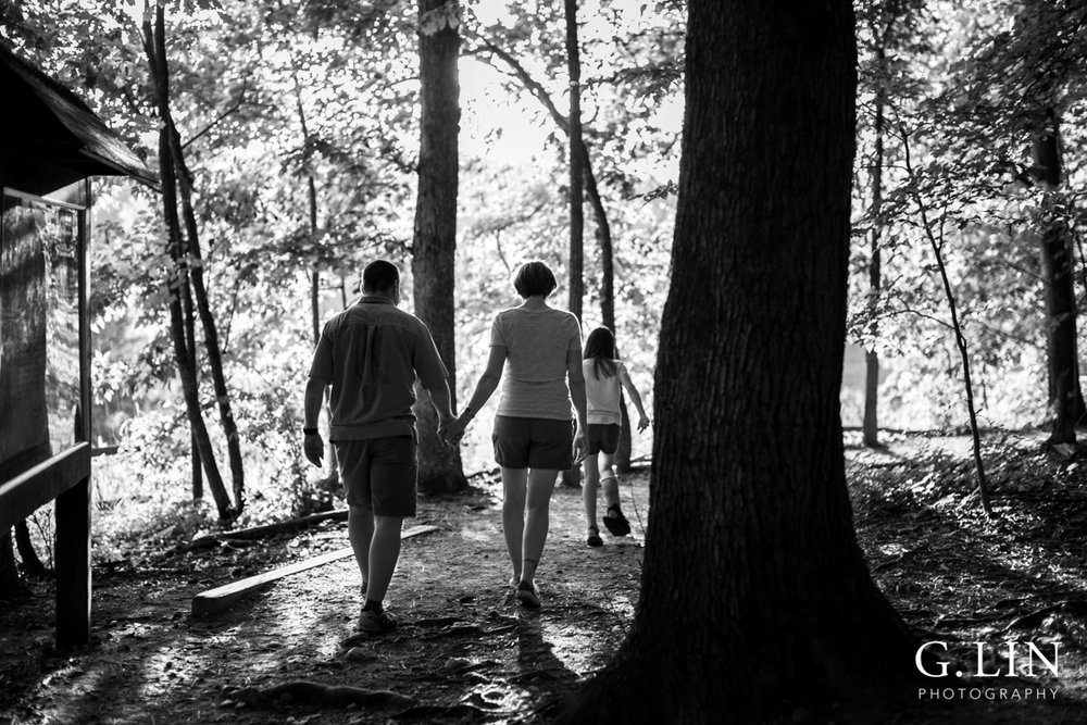 Raleigh Family Photographer | By G. Lin Photography | Black and white photo of family walking in woods