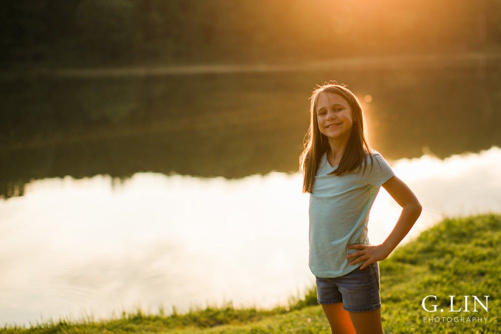 Raleigh Family Photographer | By G. Lin Photography | Girl smiling at camera by the lake during sunset