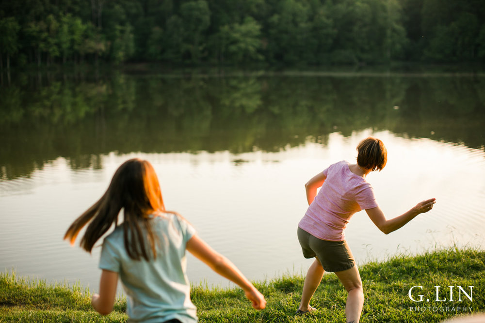 Raleigh Family Photographer | By G. Lin Photography | Mother skipping rocks on lake
