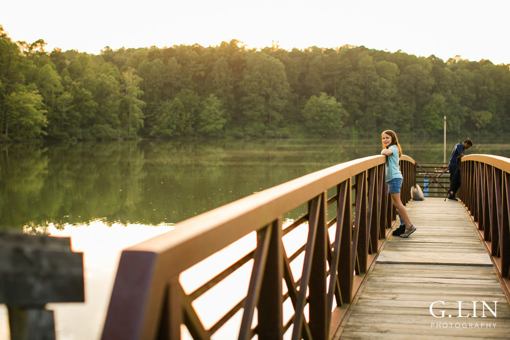 Raleigh Family Photographer | By G. Lin Photography | Girl on Umstead Park bridge looking at camera