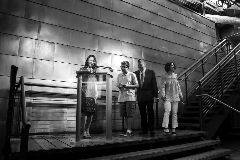 Renee Chou with a family on stage | Catwalk to Camp Fundraiser | By G Lin Photography
