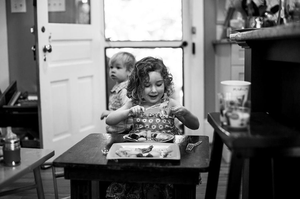 Little girl eating | Graduation Portraits for UNC Student | By G. Lin Photography | Durham Family Photographer