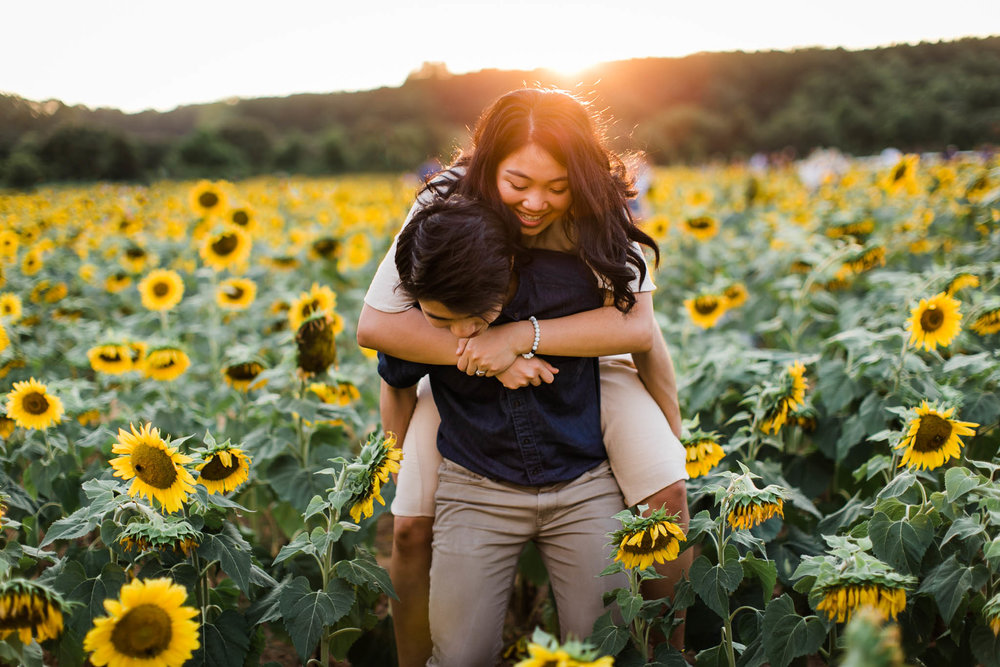 Couple walking through sunflower field at Dorothea Dix Park | By G. Lin Photography | Raleigh Engagement Photographer
