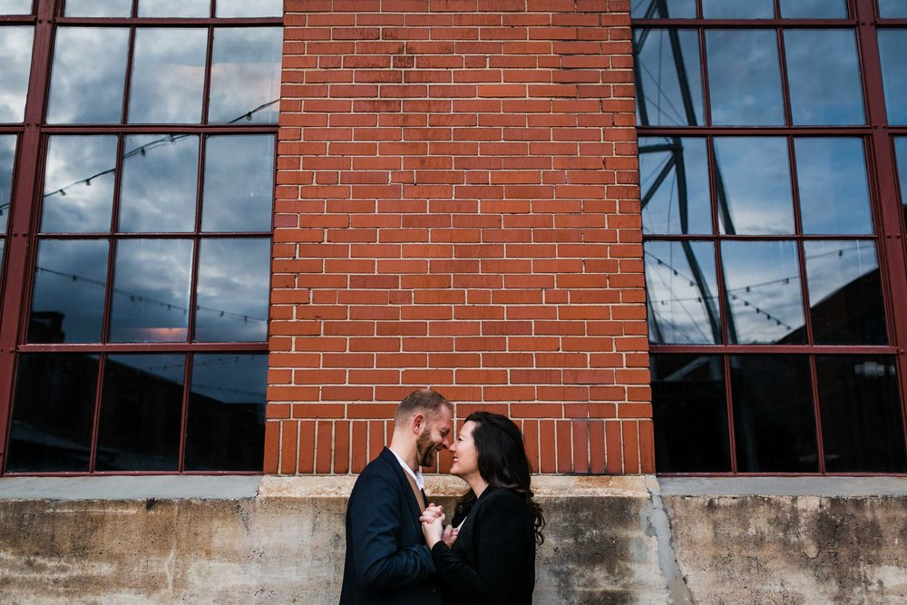 Wide shot of couple outside of brick building | American Tobacco Campus Photography in Durham, NC | By G. Lin Photography