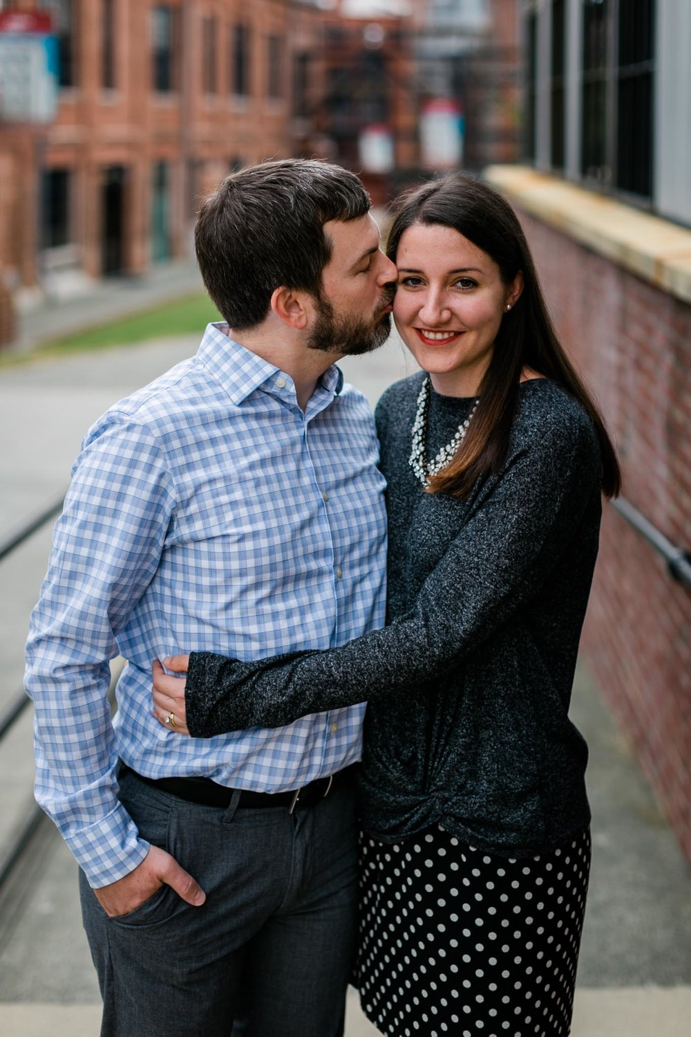 Husband kissing wife on cheek in Downtown Durham | Durham Photographer | By G. Lin Photography