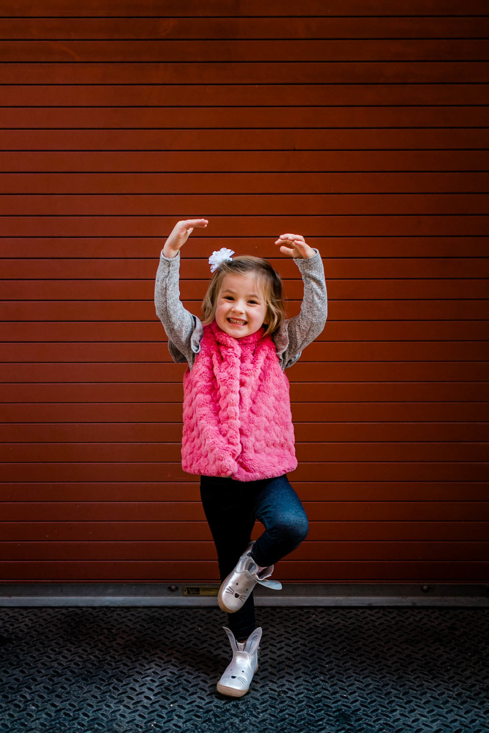 Little girl in front of red wall at The American Tobacco Campus | Durham Family Photographer | By G. Lin Photography