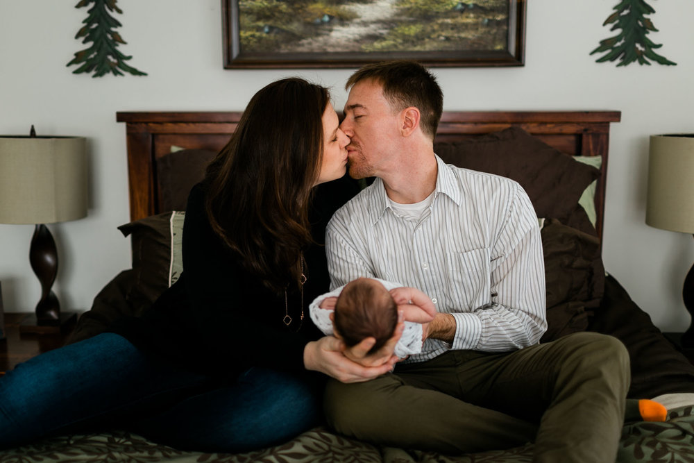Parents holding baby and kissing | Durham Newborn Photographer | By G. Lin Photography
