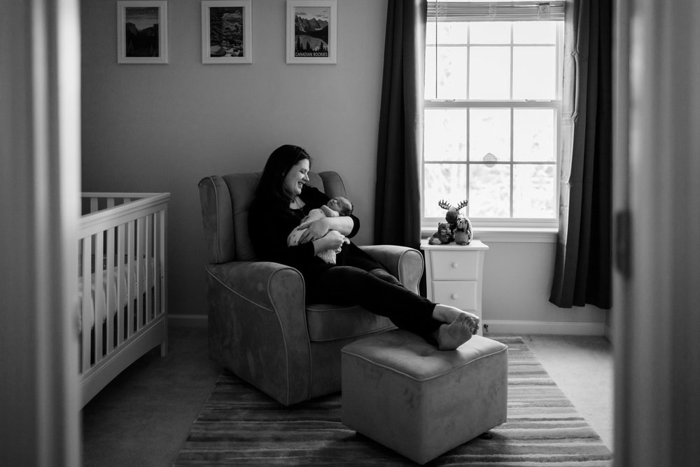 Mom sitting with baby in nursery at home | Durham Newborn Photographer | By G. Lin Photography