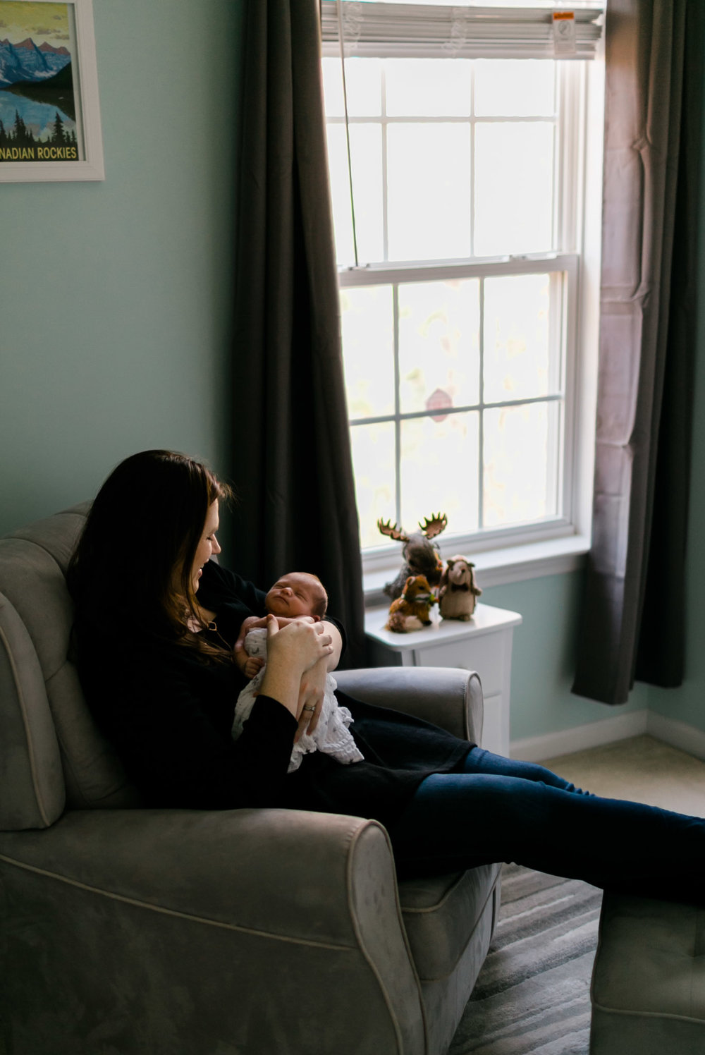 Mom sitting with baby in nursery | Raleigh Newborn Photographer | By G. Lin Photography