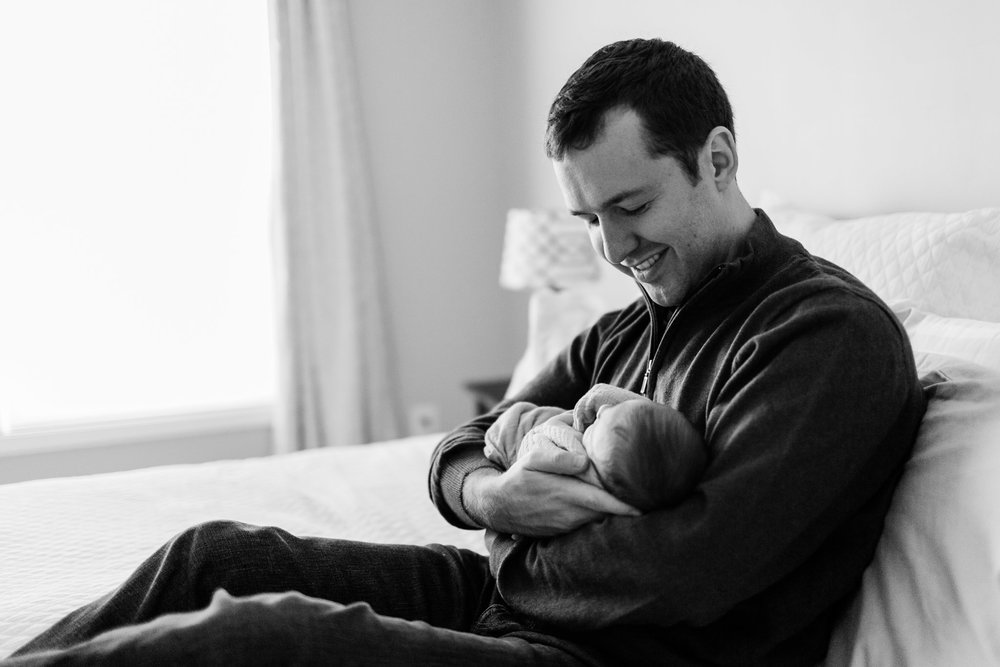 Black and white photo of father holding baby in arms | Raleigh Newborn Photographer | By G. Lin Photography