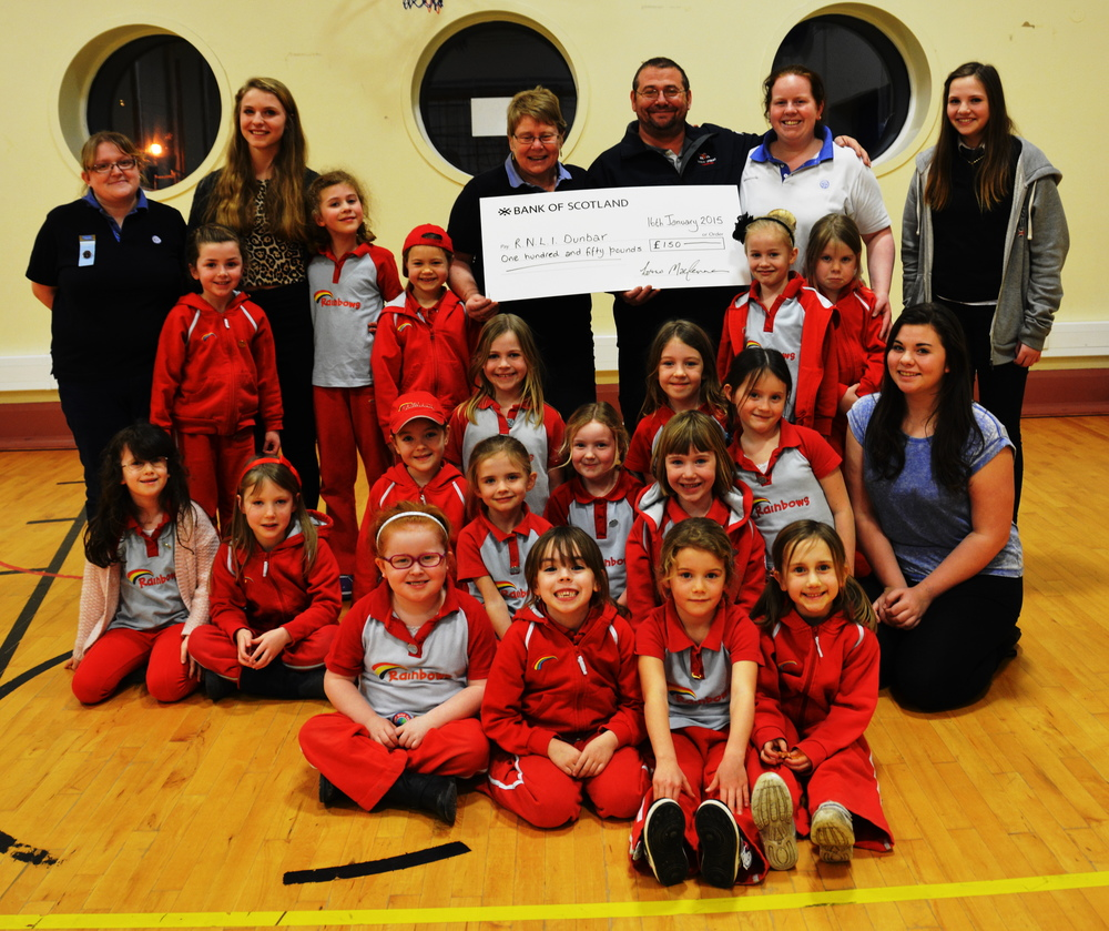 Photo; Belhaven's 1st Rainbows presenting the check to coxswain Gary Fairbairn
