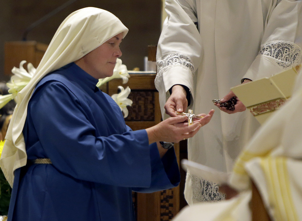 Mother Mary Catherine receiving crucifix  from His Excellency Bishop David L. Ricken after professing Final Vows