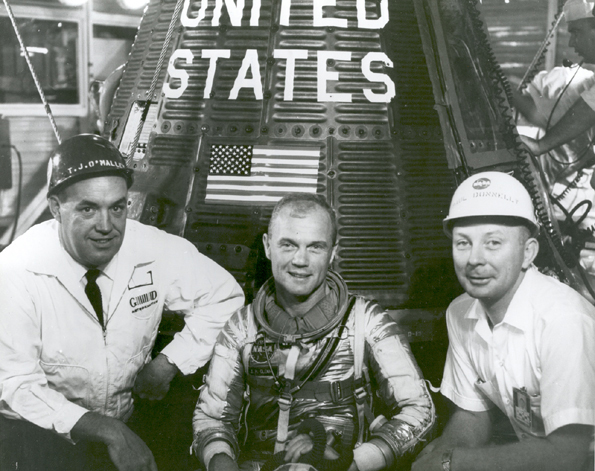 "January 24, 1962: John Glenn With T.J. O'Malley and Paul Donnelly in Front of Friendship 7. Grouped together with astronaut John H. Glenn, Jr., beside ""Friendship 7"" spacecraft are left to right: T.J. O'Malley, chief test conductor for General Dynamics; Glenn; and Paul Donnelly.  Image # : 62-MA6-58."