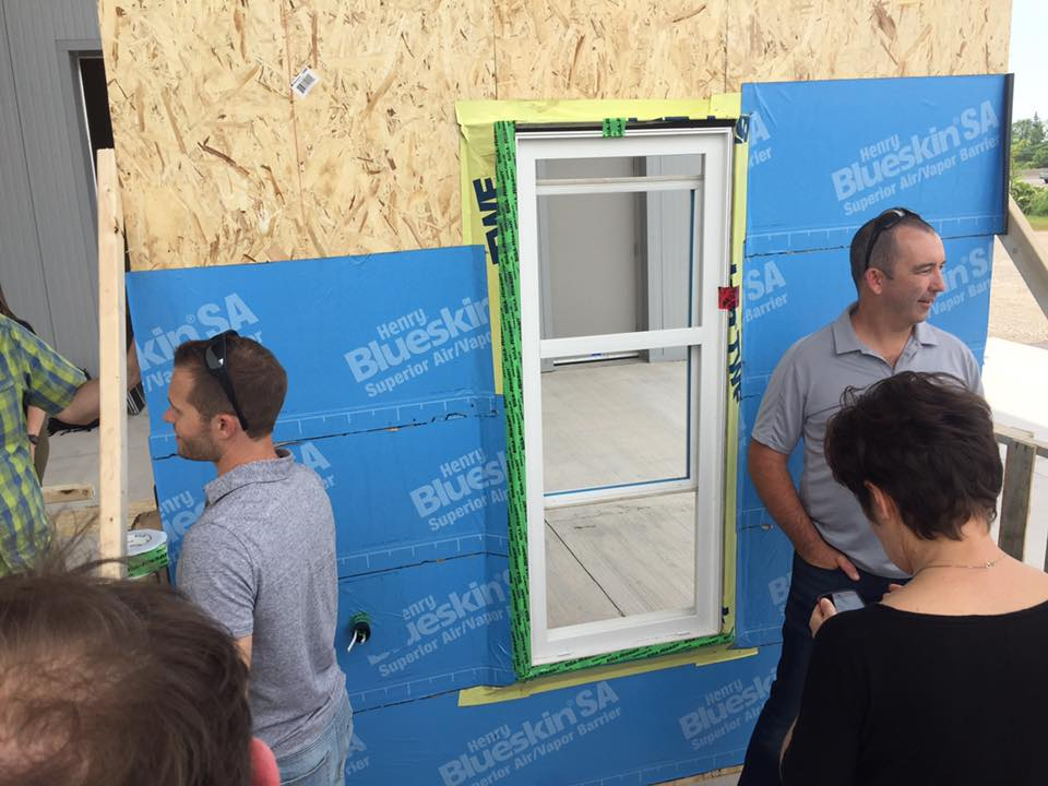 Two Fourth Pig staff in front of sample Passive House wall and window
