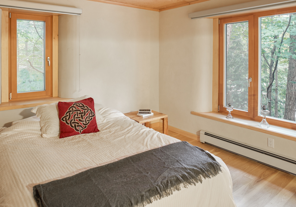 Bedroom with earth plaster walls, rounded corners around windows, wood floor.