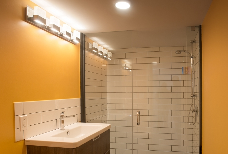 Bathroom shower with glass doors and sink, golden coloured walls