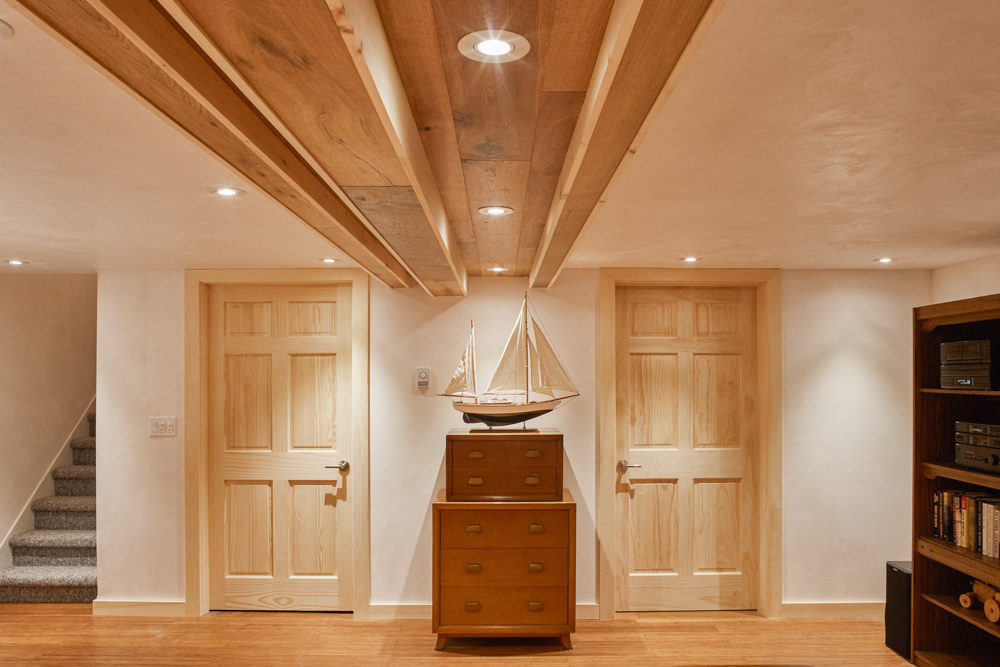 Basement two wooden doors, wood floor, white plaster floor and ceiling with LED potlights