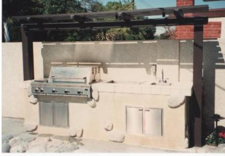 Outdoor kitchen area, stucco with granite stone accents and wood arbor.  Gilbert Residence (KRM Garden Design/Build)