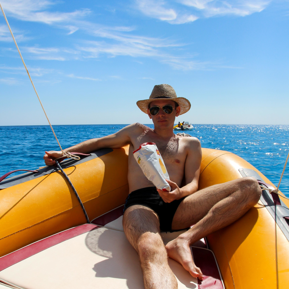 Kristian in his happy place...with a bag of chips, on a boat in the Mediterranean sea.