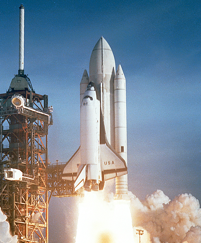 Space Shuttle  Columbia  lifting off on STS-1, her maiden flight.  Note the painted external fuel tank.  This would be left unpainted in future missions.
