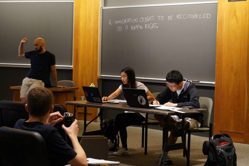 Curriculum Director Christian Tarsney moderates a demo debate between instructors Anne-Marie Hwang and Lawrence Zhou.