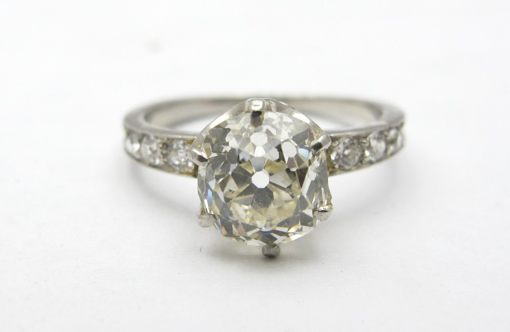 Platinum setting with EGL certified 2.05ct J color, VS2 clarity old mine cut center diamond and old European accent diamonds.
