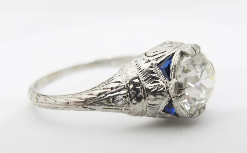 Hand-engraved platinum setting with synthetic sapphire and diamond accents. Center diamond is GIA certified 1.42 carats, I color and VS1 clarity. c. 1925.